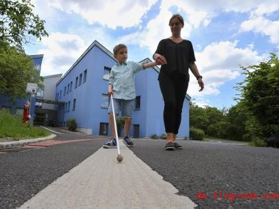 Der taubblinde Lucas läuft mit seinem Blindenstock und seiner Erzieherin Stefanie Tröster vor dem Blindeninstitut. Foto: Karl-Josef Hildenbrand/dpa