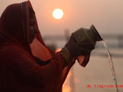 Diese gläubige Frau gießt Wasser aus einem Krug, um den So<em></em>nnengott und seine Frau anzubeten. F. Foto: Sunil Sharma/XinHua/dpa
